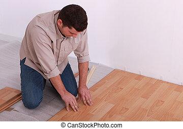 hombre que coloca, un, piso de madera