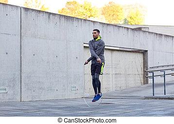 hombre que ejercita, con, saltar-cuerda, aire libre