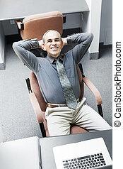 hombre que sienta, en, escritorio de oficina