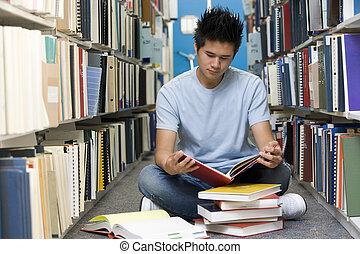 hombre que sienta, en, piso, en, biblioteca, libro de...