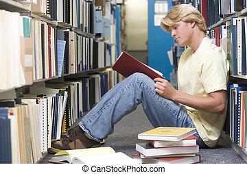 hombre que sienta, en, piso, en, biblioteca, libro de lectura