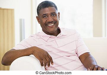 hombre que sienta, en, sala, sonriente