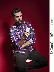 hombre que sienta, en, silla, y, utilizar, teléfono móvil