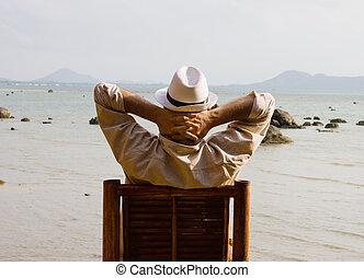 hombre que sienta, en, un, silla, y, mira, el, mar