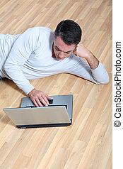 hombre que sienta, sobre el piso, con, computadora de computadora portátil