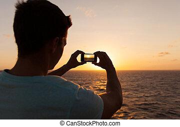 hombre, saque fotografía, de, puesta sol mar