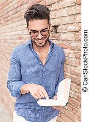 hombre sonriente, leer un libro, y, puntos, a, él