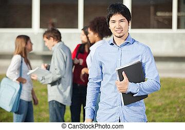 hombre, tenencia, libro, con, estudiantes, en, plano de fondo, en, campus