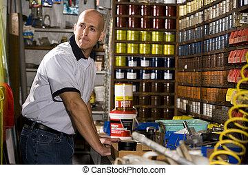 hombre, trabajando, en, tienda impresión, por, estantes, apilado, con, tintas