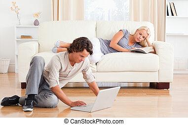 hombre, utilizar, un, computador portatil, mientras, el suyo, novia, es, leer un libro