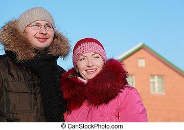hombre y mujer, sonriente, en, invierno, aire libre, casa, ladrillo rojo, cielo azul