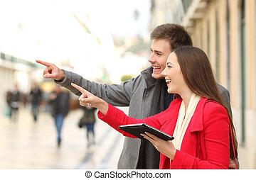 hombre y mujer, teniendo tableta, señalar, lejos, en, el, calle