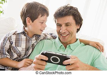 hombre, y, niño joven, con, portátil, juego, sonriente