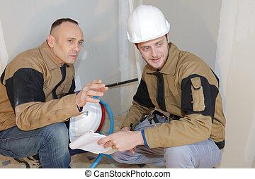 hombres, agachar abajo, en, sitio del trabajo