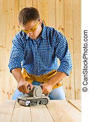 hombres jóvenes, trabaja, con, detalle, lijadora