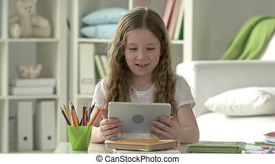 Home Alone - Female youngster playing games on digital...