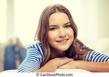 smiling teenage girl lying on sofa at home