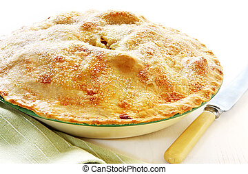 Home-baked apple pie, straight from the oven, in vintage enamel pie plate. With bone-handled knife, ready for cutting.