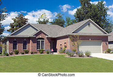 Home - Beautiful brick ranch home against a blue cloudy sky....