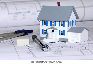 Miniature House With Various Drafting Items and Blue Prints.
