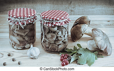 Home canning: pickled mushrooms in glass jars.
