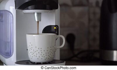 Home capsule coffee machine prepares a cup of fresh coffee. Cloud of steam at the end of cooking