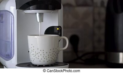 Home capsule coffee machine prepares a cup of fresh coffee...