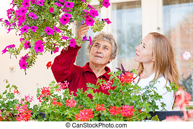 Elderly woman shows her flowers to her assistant