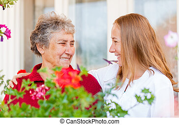 Home care - Happy elderly woman and her helpful assistant