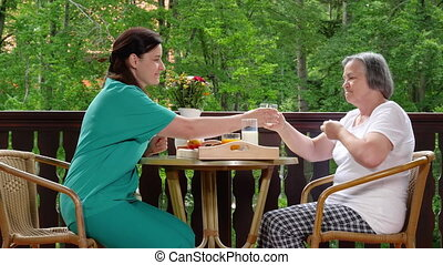 Home caregiver giving medicine to senior woman - Nurse...