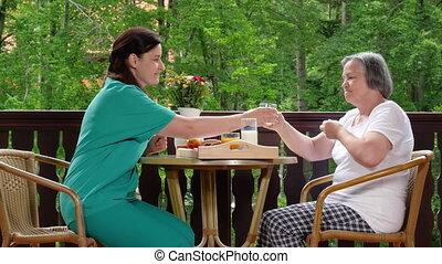 Home caregiver giving medicine to senior woman