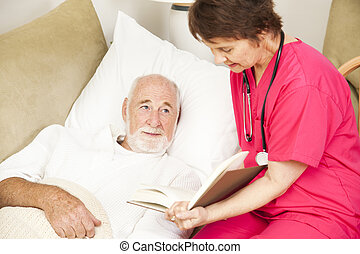 Friendly home caregiver reads to an elderly patient.