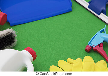 home cleaning products on green background with space