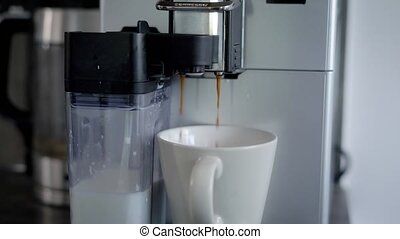 home coffee making machine is producing cappuccino in...