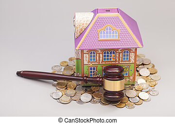 Home, coins and gavel isolated on gray.Real estate concept