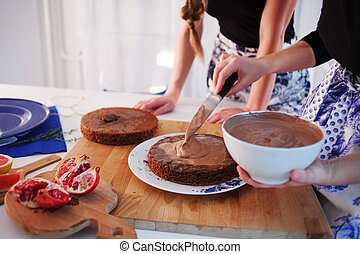 Home confectionery. Two girls making a cake on the kitchen. ...