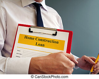 Home Construction Loan form and manager with pen.