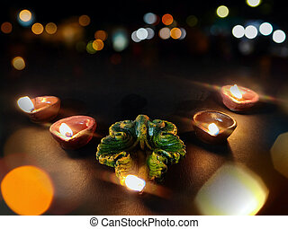 Home decoration using oil lamp or diya arranged in row for Diwali celebrations , selective focus on deep , black background