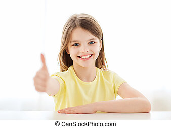 beautiful little girl at home showing thumbs up