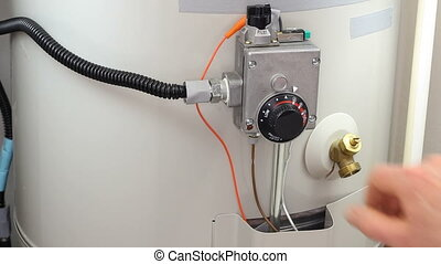 Hand of a man seen turning down house gas water heater temperature dial.