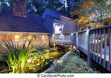 House exterior with porch walkay over a pond and lighting in the woods