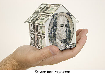 Home Equity - Horizontal shot of a man holding a small house...