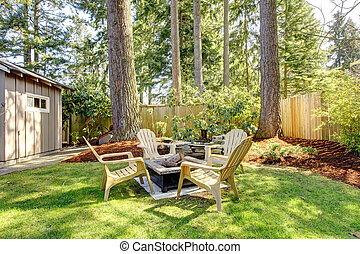 Home exterior Backyard with chairs and pine trees. Spring.