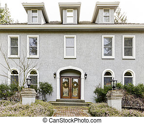 Home exterior of large grey classic house with many narrow windows.