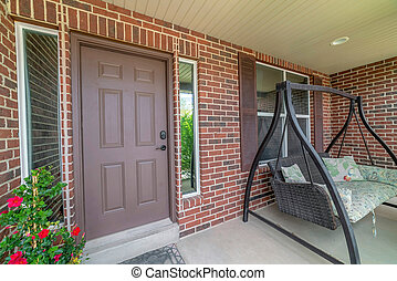 Home facade with brown front door between sidelights and swing bench on porch