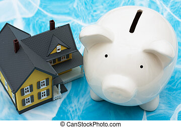 Home Finances - Model house with piggy bank on blue ...