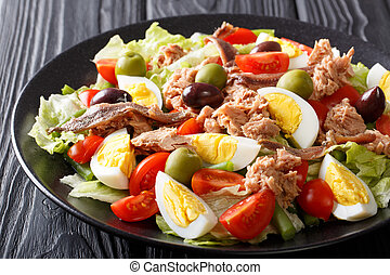 Home fish nicoise salad of tuna, anchovies, eggs and vegetables close-up on a plate. horizontal