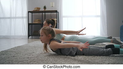 home fitness training of sporty family, mother and daughter are training together in living room, gymnastics