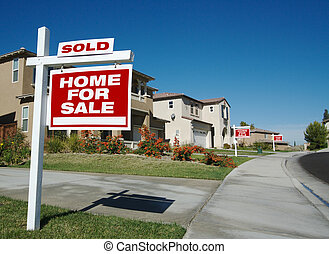 Home For Sale Signs & One Sold in Front of Beautiful New Homes