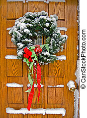 Home For The Holidays - Snow covered wreath on front door of...